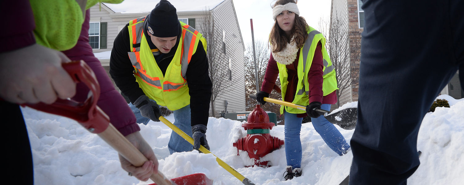 Students and a staff member from Kent State use snow shovels and regular dirt shovels to clear snow away from a fire hydrant in the city of Kent.