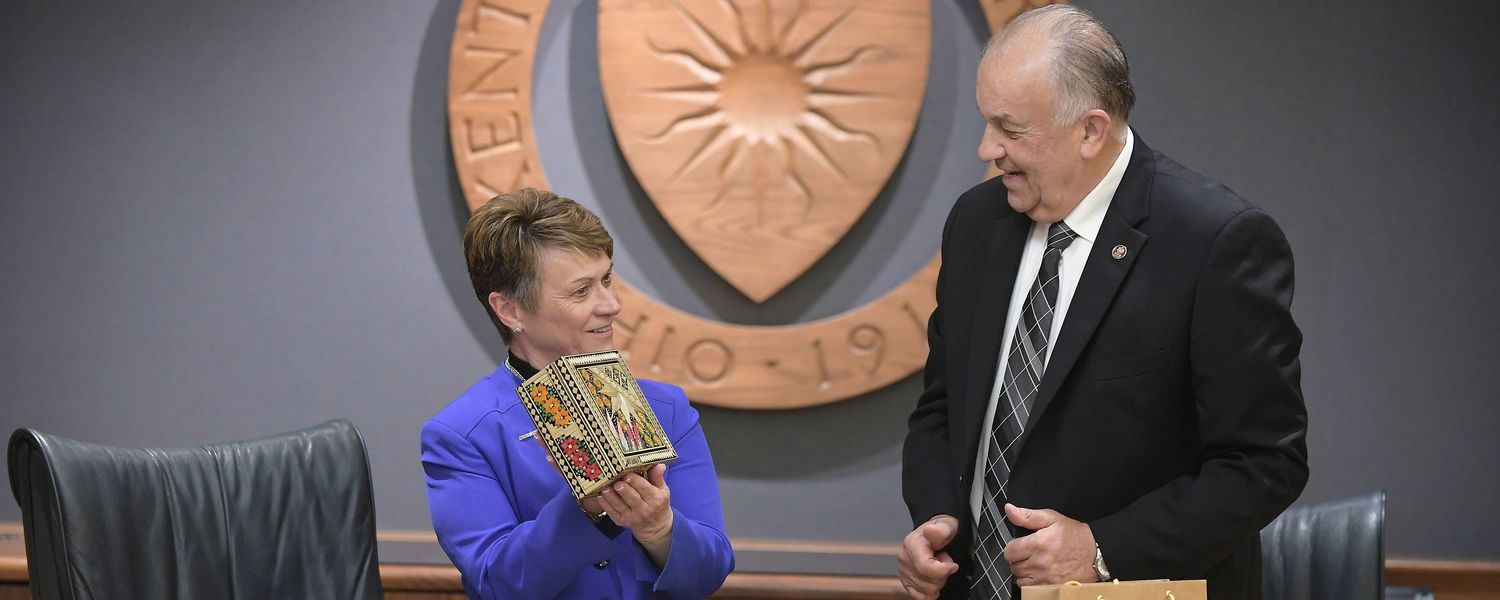 Kent State University President Beverly J. Warren displays a gift presented to her by Pontifical Catholic University of Paraná President Waldemiro Gremski following the signing ceremony between the two universities.