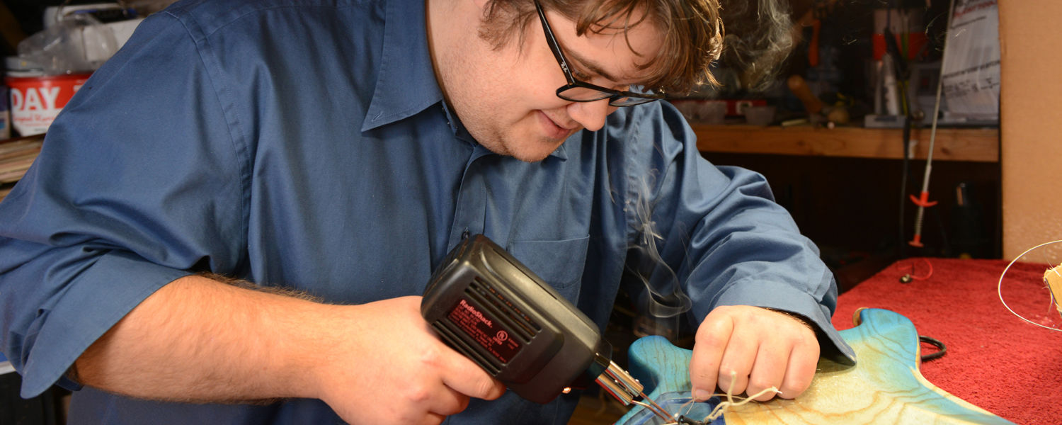 Kent State student Ryan Schoeneman solders the connections to the various switches and dials that help create the sound an electric guitar makes.