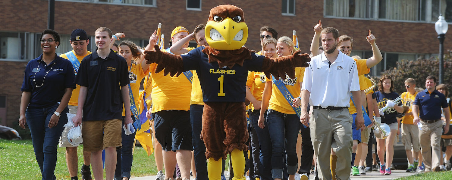 """Kent State University's mascot """"Flash"""" leads the way toward Tri-Towers as the Kent State Marching band, as well as members of the university community, walk across campus, collecting participants for the Homecoming pep rally, held on the Student Green."""