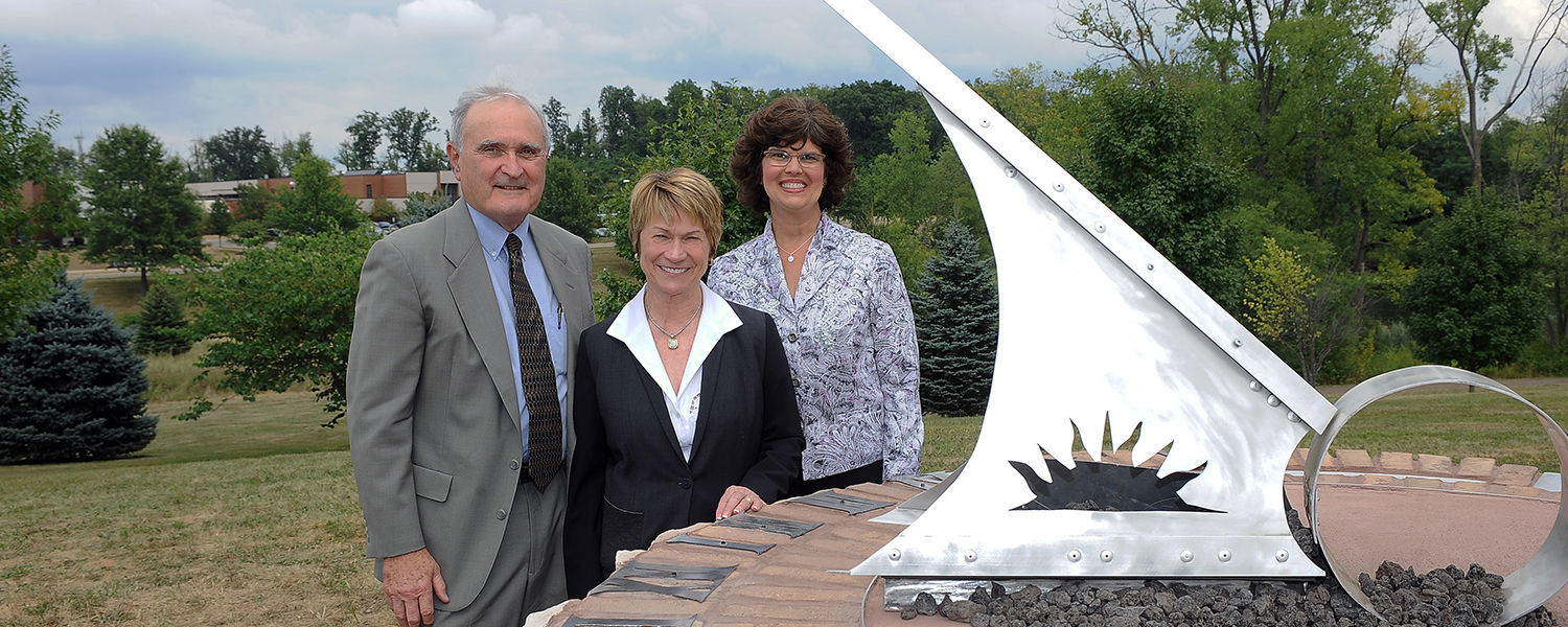 (From left to right) Dr. John Humphrey Jr., chair of the Stark Campus Advisory Board, Kent State President Beverly Warren and Kent State Stark Interim Dean Denise Seachrist gather around the new sundial, dedicated with the Science and Nursing Building.