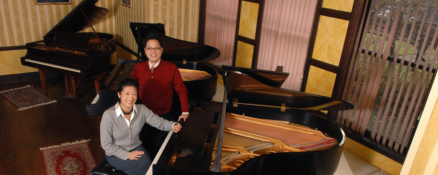 Music professors Jerry Wong and Donna Lee with Steinway pianos at Steinway Hall, in Akron.