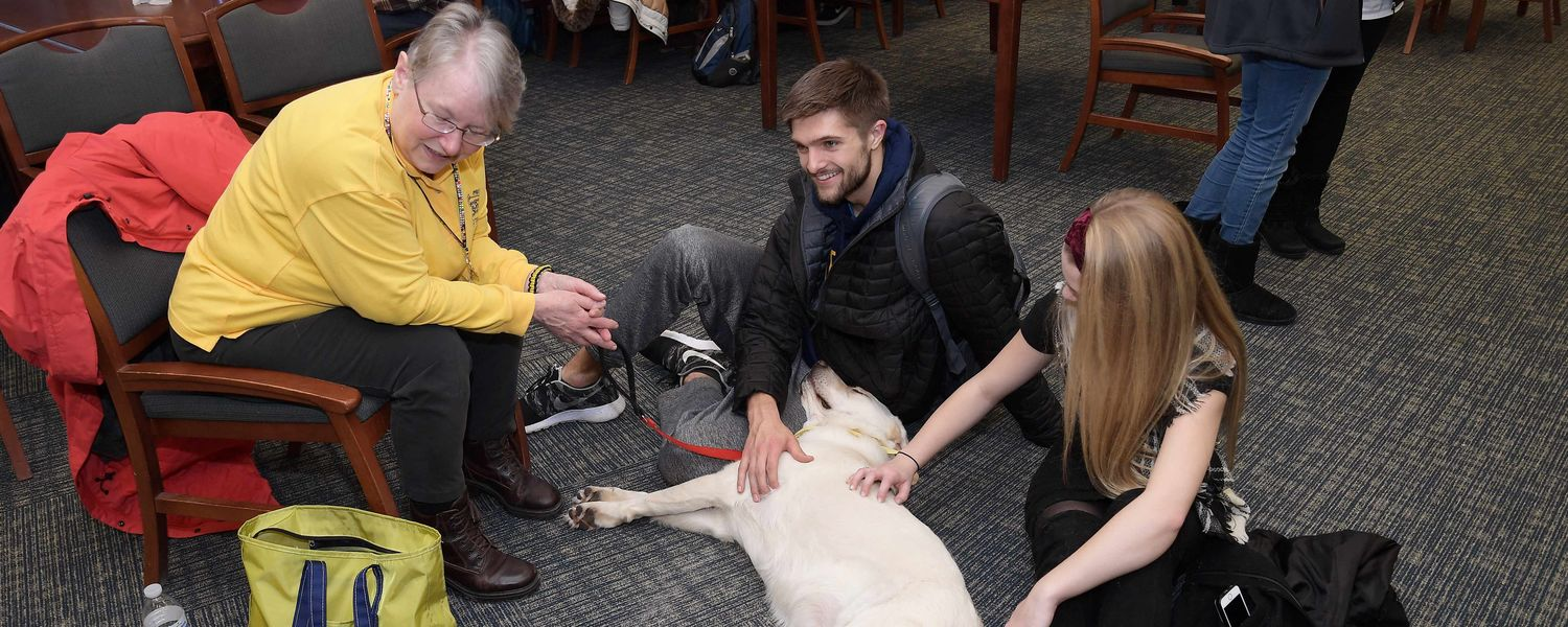 A Kent State student attending the Stress-Free Zone in the library laughs as he tries to figure out how he will eventually stand up after one of the dogs fell asleep on his lap as he was petting him.
