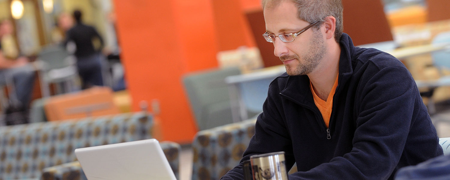 A Kent State student works on his class assignments in the library.