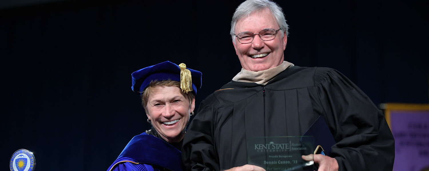 Kent State alumnus and commencement speaker Dennis Cuneo shares a lighthearted moment with Kent State President Beverly J. Warren while receiving a Distinguished Alumni Award in the Memorial Athletic and Convocation Center (MAC Center).