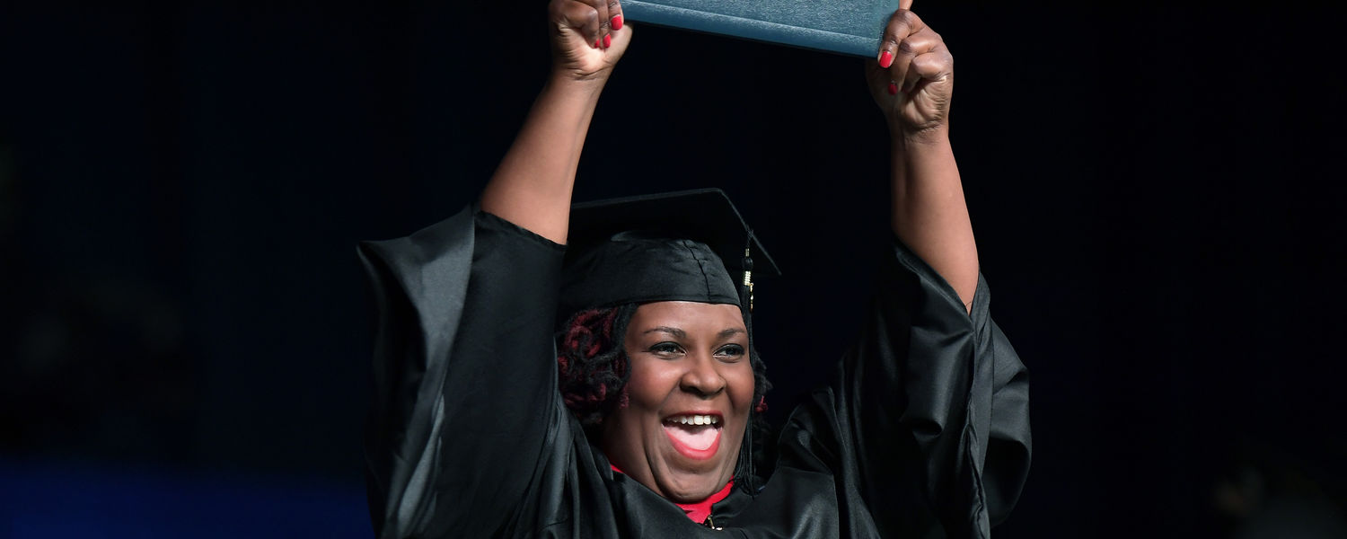 A happy graduate exits the stage with diploma in hand during the Summer 2017 Commencement ceremony in the Memorial Athletic and Convocation Center (MAC Center).