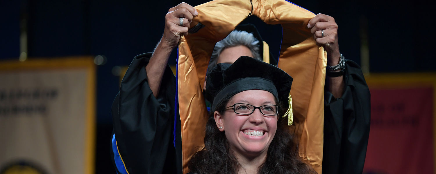 A doctoral candidate is hooded by her advisor during the advanced degree ceremony during the Summer 2017 Commencement ceremony in the Memorial Athletic and Convocation Center (MAC Center).