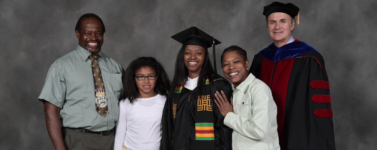 A graduate and her family pose for keepsake photos with Provost Todd Diacon following Summer 2017 Commencement ceremonies in the Memorial Athletic and Convocation Center (MAC Center).