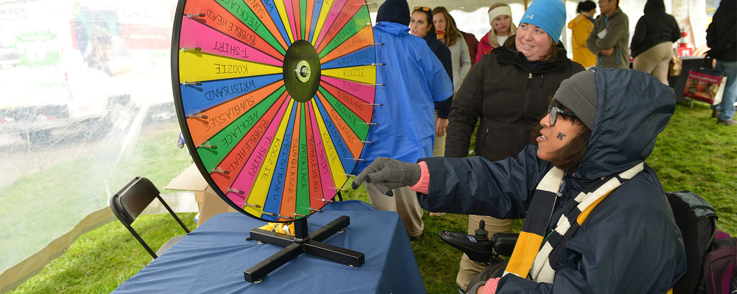 A Kent State student spins a wheel to win a prize during Homecoming.