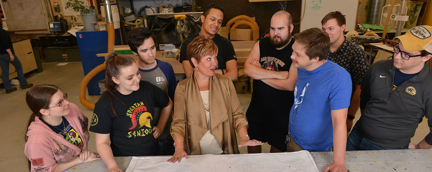 Terri Kent (center), professor of theatre in Kent State's College of the Arts, goes over a stage plan with students in the scene shop.
