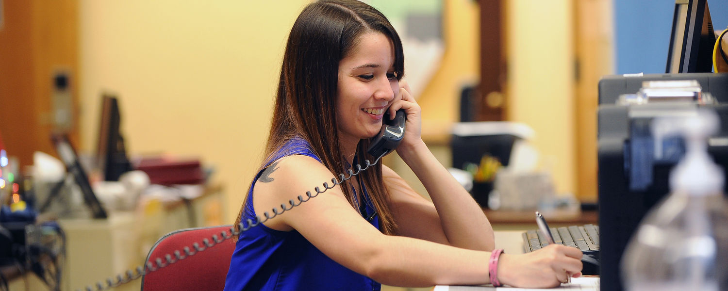 Kent State student Theresa Medrano responds to a question during a phone call while at work in the FLASHcard office in the Kent Student Center.