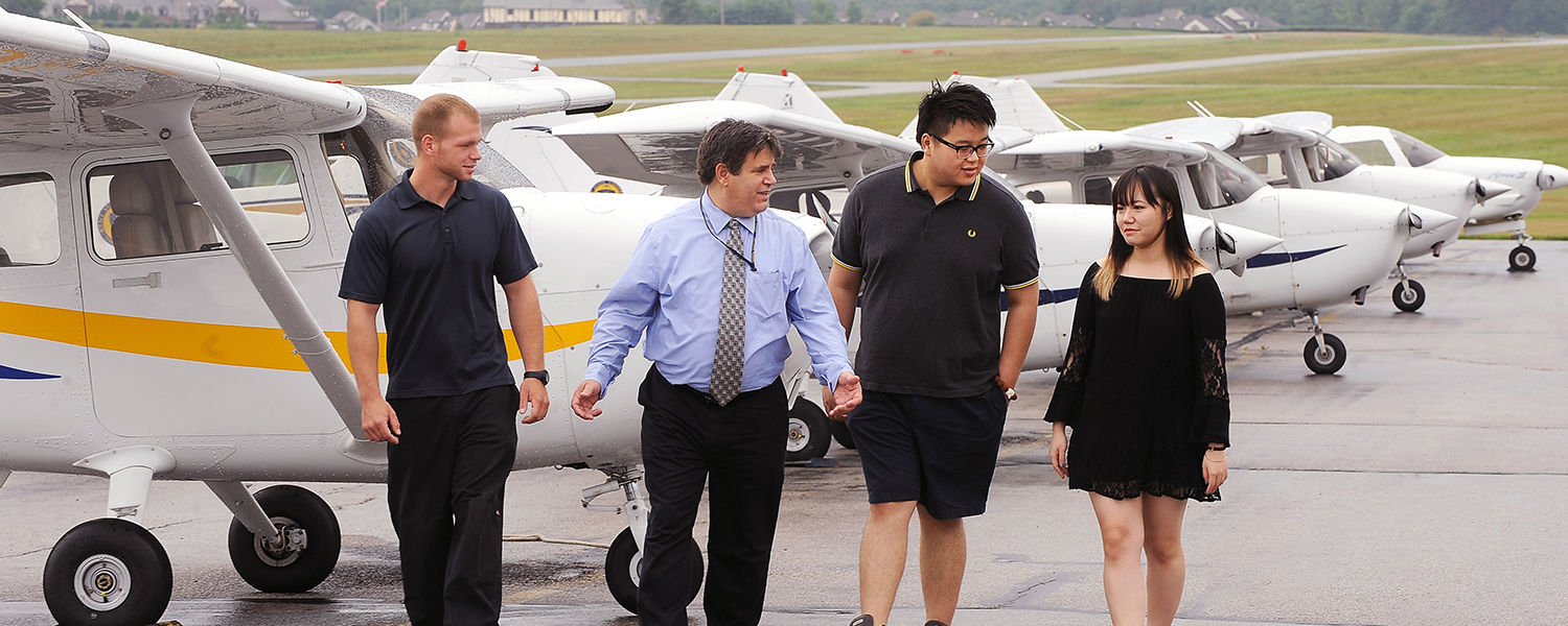 Thomas Long (second from left), assistant professor in the College of Applied Engineering, Sustainability and Technology, walks along the flight line at the Kent State University Airport with a group of Kent State students.