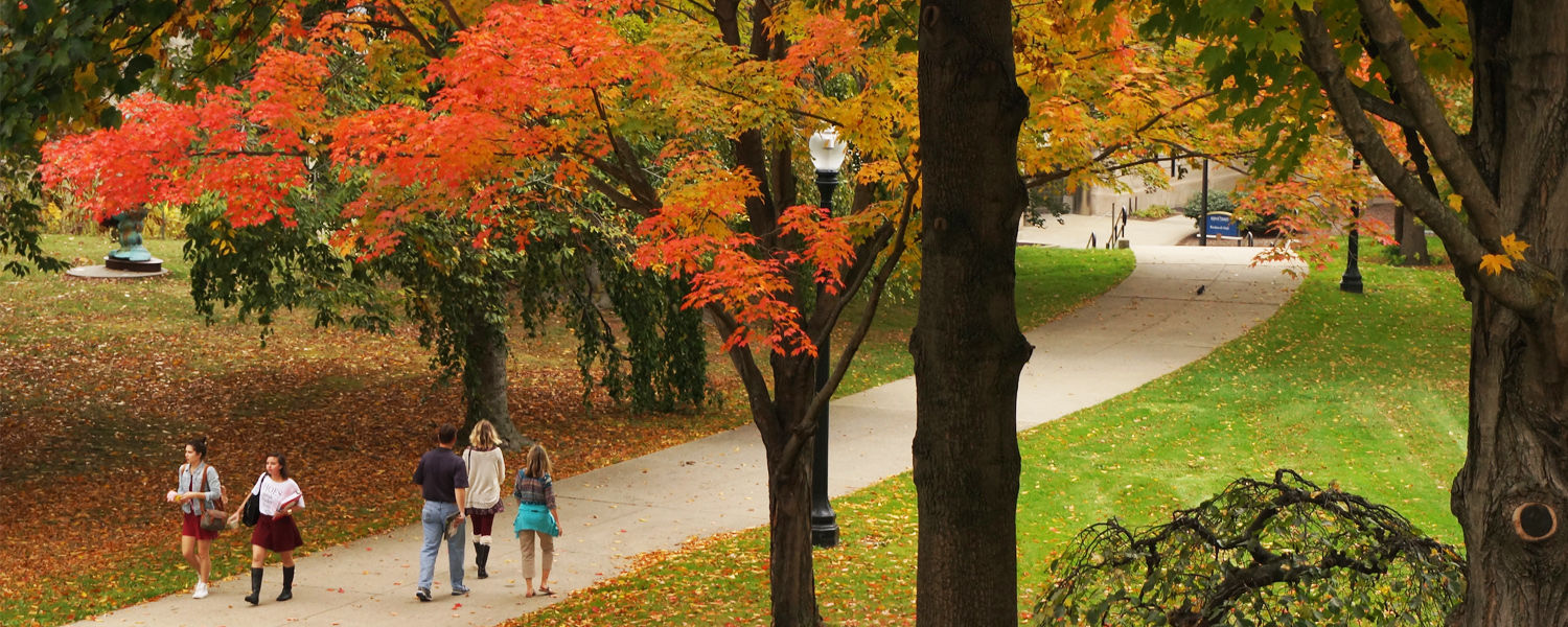 Students and parents walking through campus in the fall