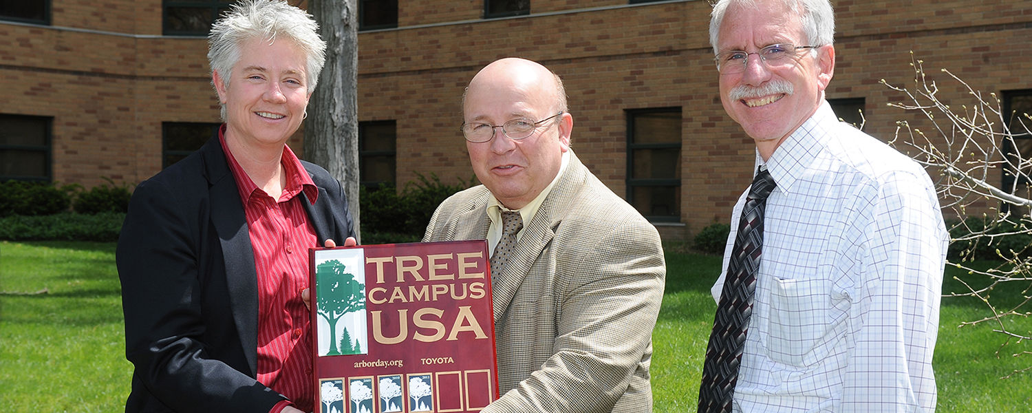 Kent State's Grounds Manager Heather White, Senior Vice President for Finance and Administration Gregg Floyd and Associate Vice President for Facilities Planning and Operations Tom Euclide accept Kent State's designation as an official Tree Campus USA.