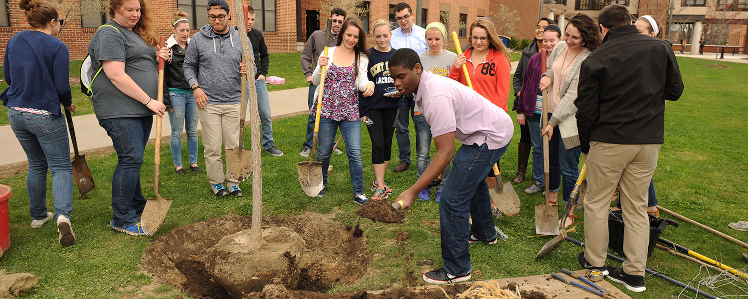 Kent State students plant a tree behind Stopher Hall during the university's annual Arbor Day celebration.