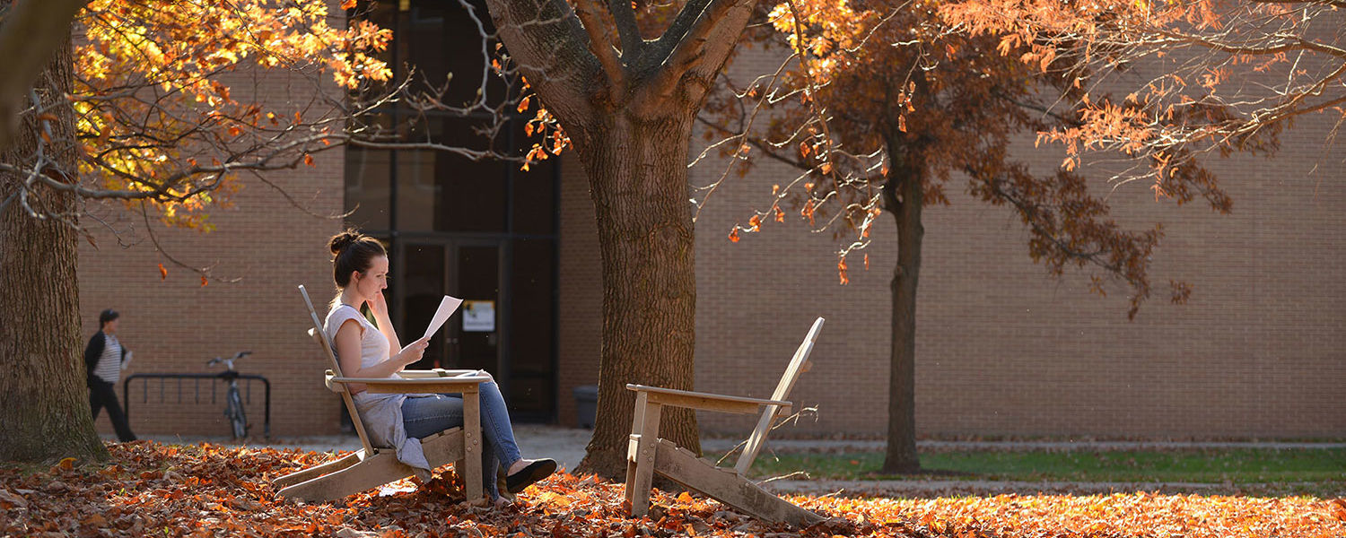 A Kent State student sits in the shade of a magnolia tree behind Henderson Hall.