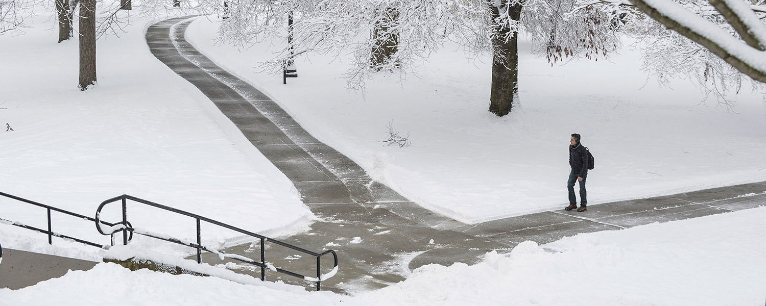 A Kent State University student walks past snow-covered trees near Rockwell Hall after the first heavy snowfall of 2016.