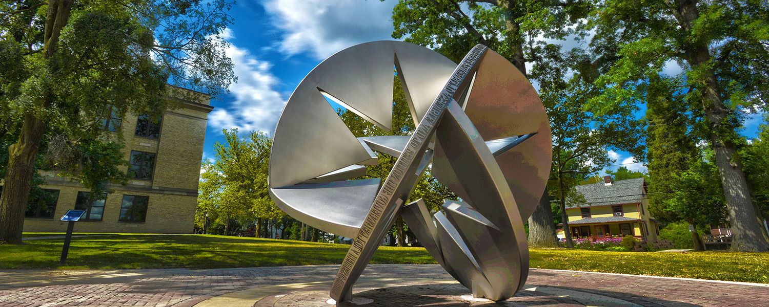 Public art on front campus, near tall trees by Franklin Hall, is part of the Sculpture Walk along the Lefton Esplanade.