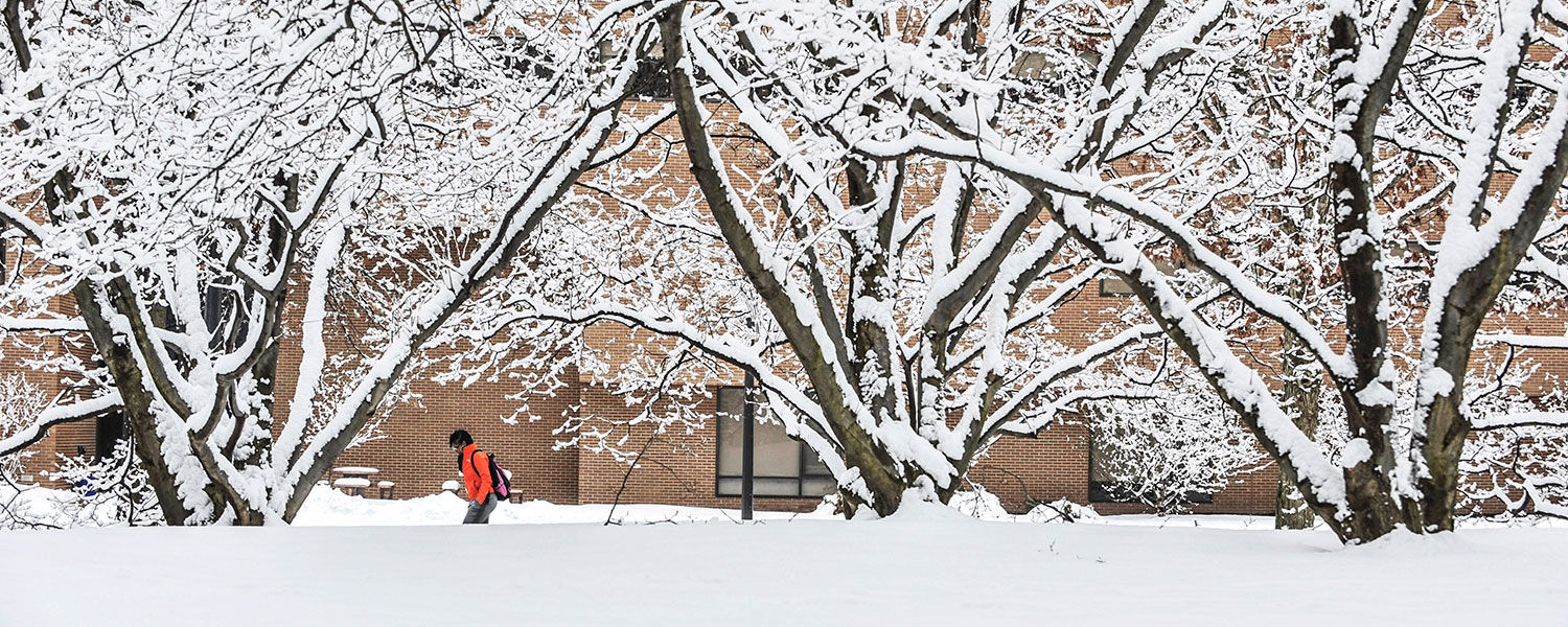 A passing Kent State student adds color to a snowy scene near trees behind Henderson Hall.