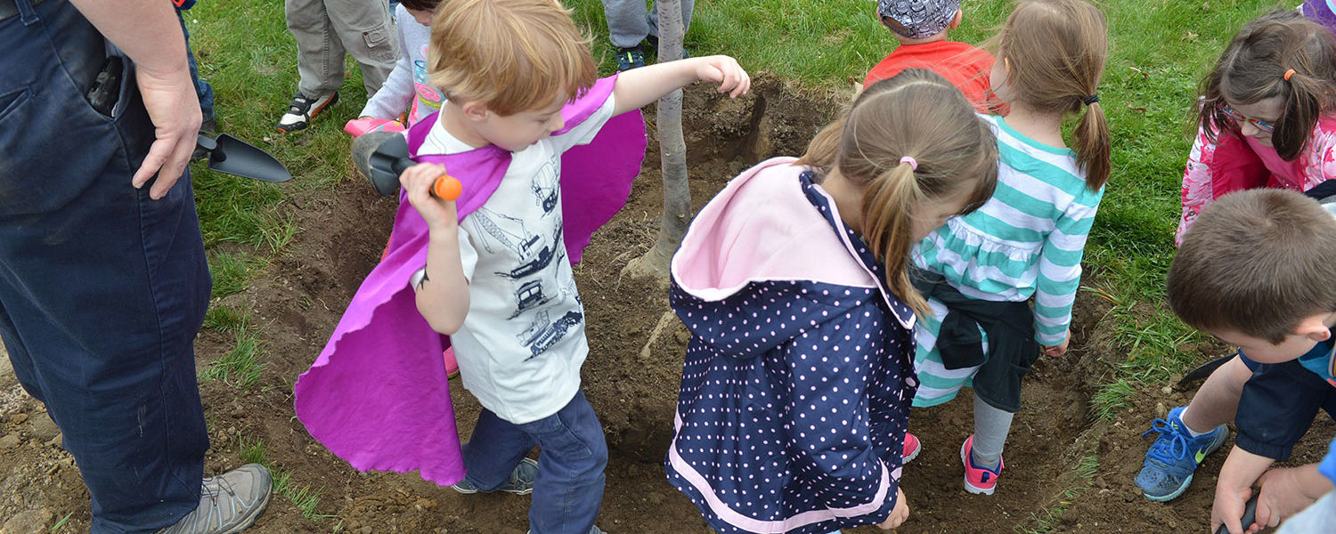 Children from Kent State's Child Development Center tamp the dirt around a tree they just helped plant for the university's 2016 Arbor Day celebration.