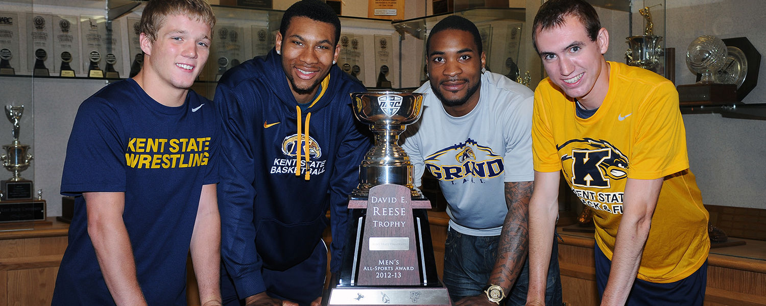 Kent State student-athletes gather around the 2012-13 Reese Trophy in the Memorial Athletic and Convocation Center. Pictured are wrestler Mack McGuire, basketball player Devareaux Manley, football wide receiver Tyshon Goode and cross country runner Samuel