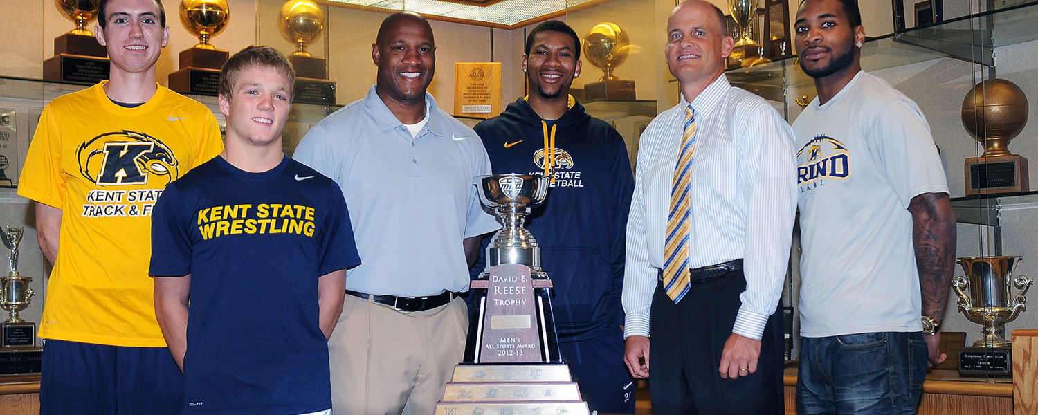 (left to right) Kent State's Samuel Allen, Mack McGuire, head football coach Paul Haynes, Devareaux Manley, Director of Athletics Joel Nielsen and Tyshon Goode gather around the 2012-13 Reese Trophy in the Memorial Athletic and Convocation Center.