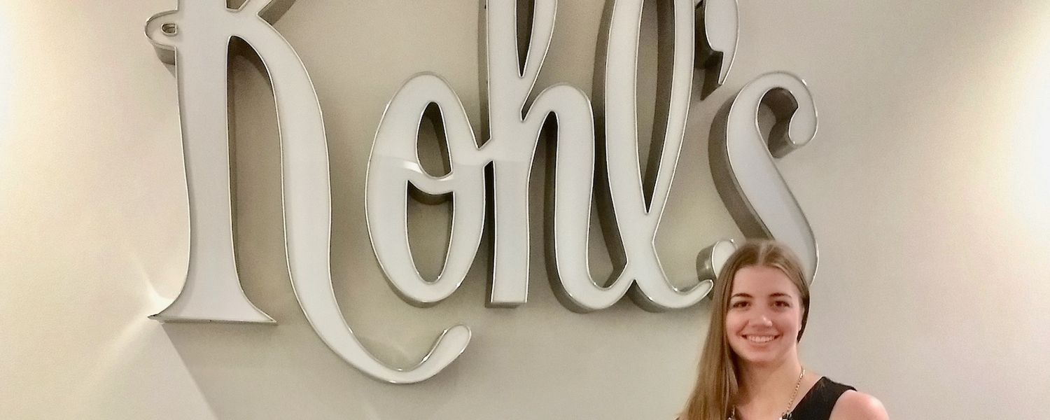 Honors Student Sitting with Kohl's Sign at Internship