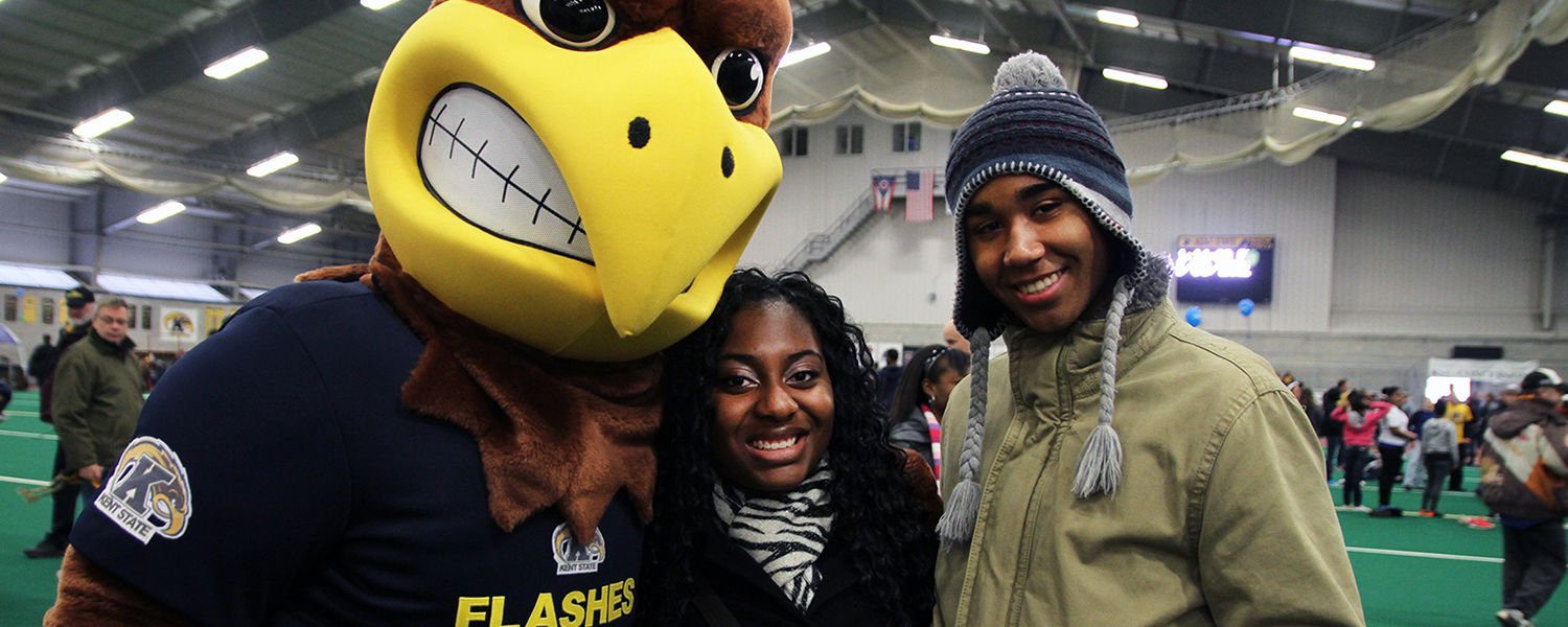Upward Bound high school students pose with Flash, the Kent State mascot, at a lunch at the Kent State Field House.