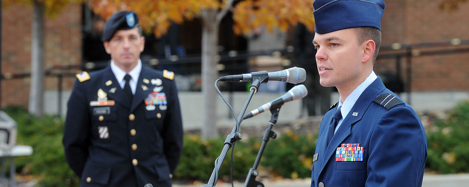 Kent State student Andrew Altizer speaks on behalf of veterans during university's 2013 Veterans Day observance on Risman Plaza. Listening to Altizer is Lt. Col. Mark Piccone of the Kent State ROTC.