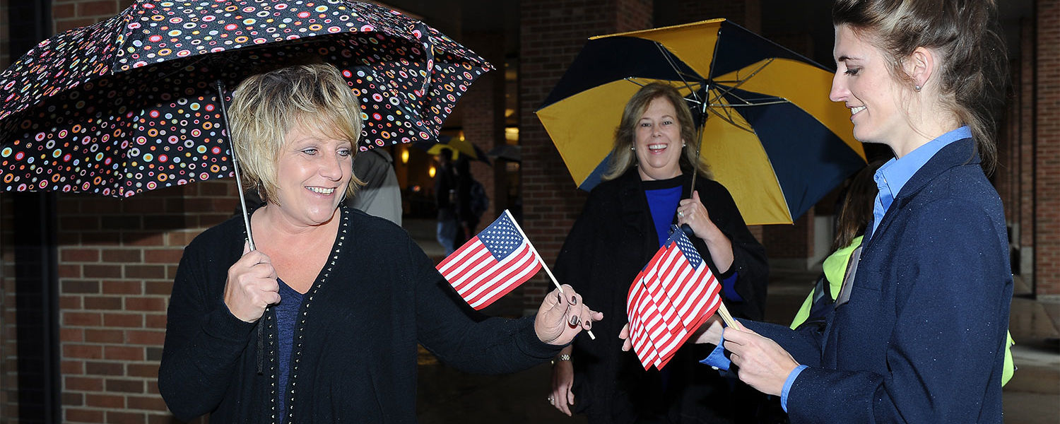 Kent State Student Ambassadors distribute small American flags to those attending the university's annual Veterans Day observance.