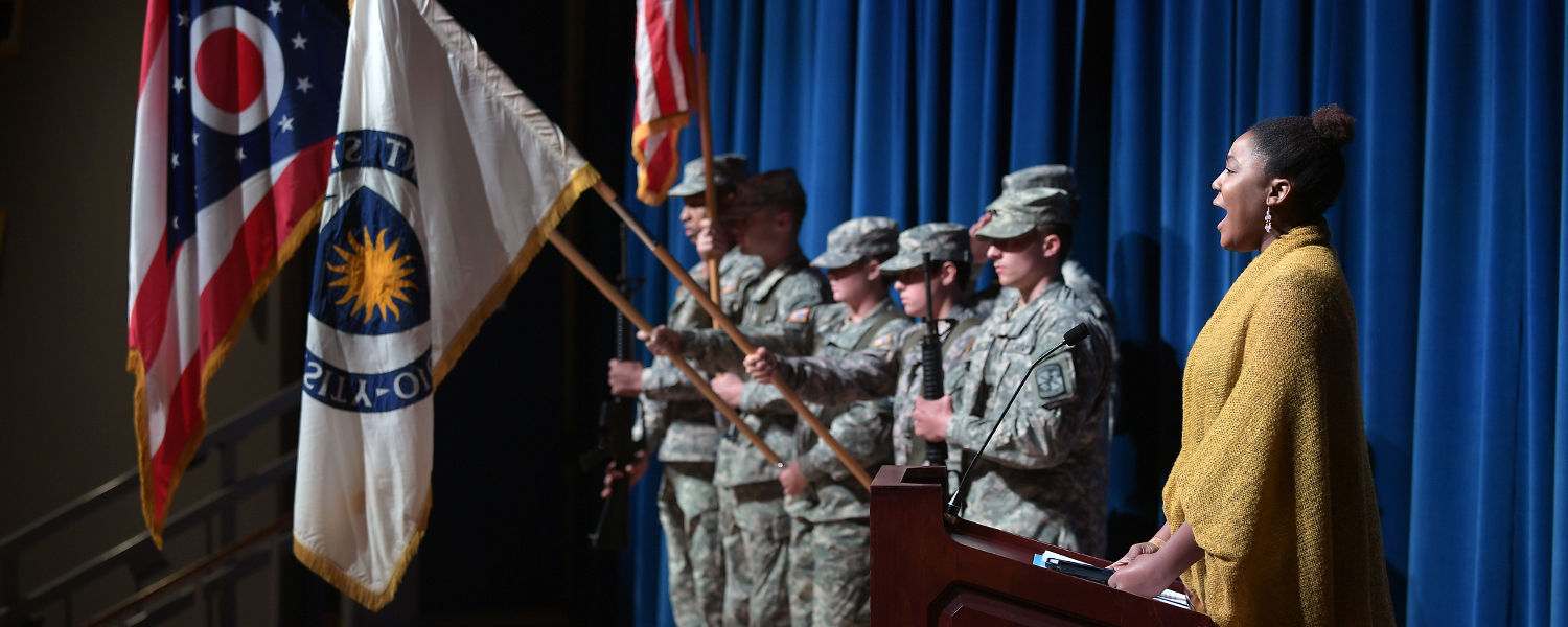 A Kent State student sings the national anthem at the start of the university's annual Veterans Day observance at the Kent Student Center Kiva.