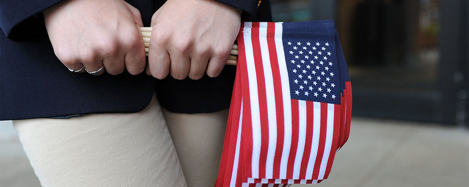 A Kent State student ambassador grips a handful of American flags as she awaits attendees for the annual Veterans Day observance.