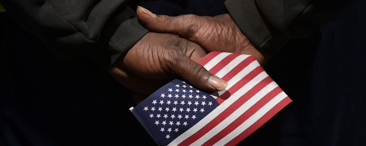 A Kent State employee and veteran stands at attention and grips an American flag during the singing of the national anthem during the university's annual observance of Veterans Day held at the Kent Student Center Kiva.
