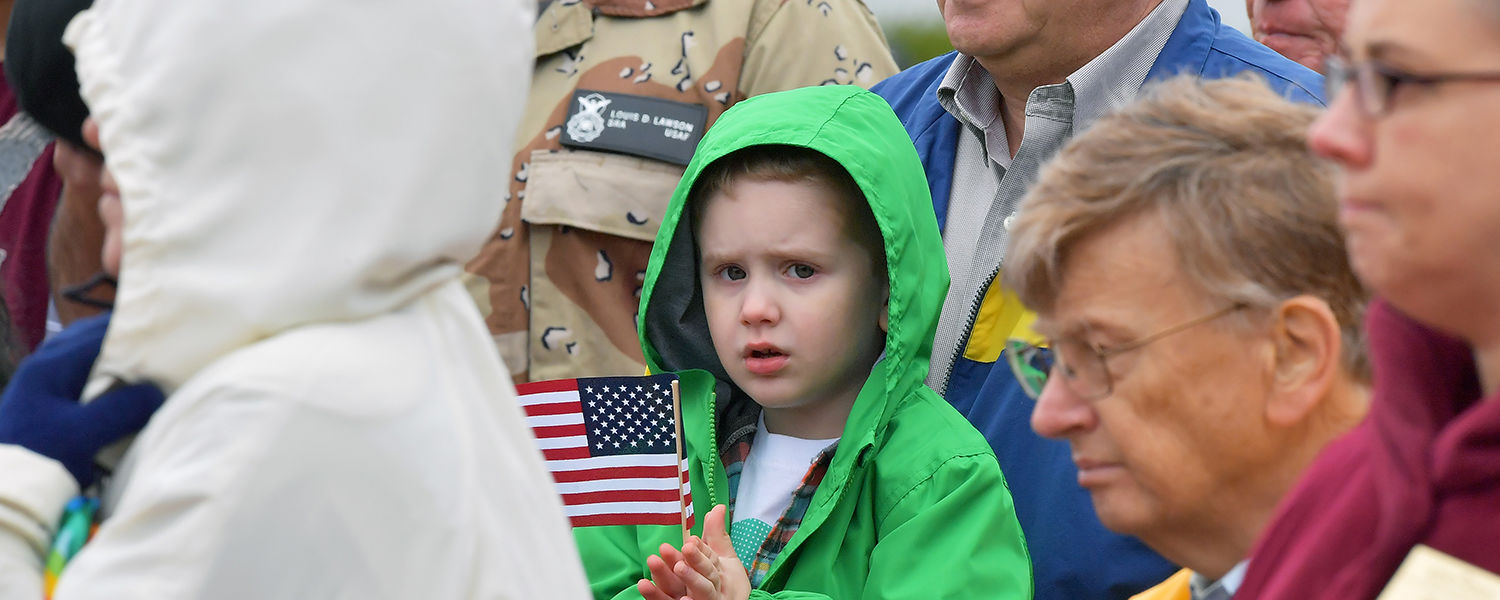 A child displays his American flag during Kent State's observance of Veterans Day.