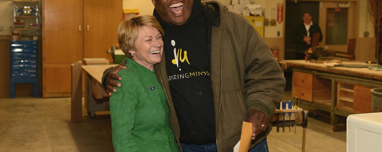 Kent State President Beverly Warren hugs Joseph Walker as he wins a President's Excellence Award.