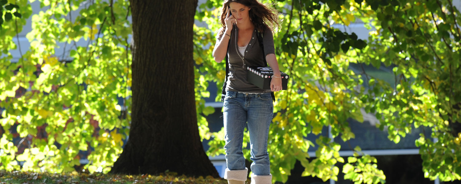 A Kent State student makes a phone call during a walk between classes on campus.