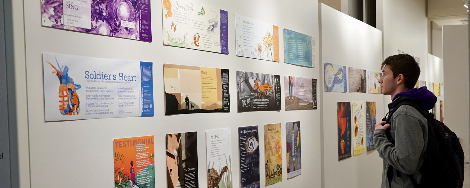 Student looking at a selection of 10 years of Traveling Stanzas Posters