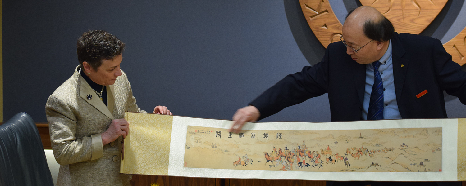President Junzhe presents President Warren with a painted scroll depicting the Silk Road