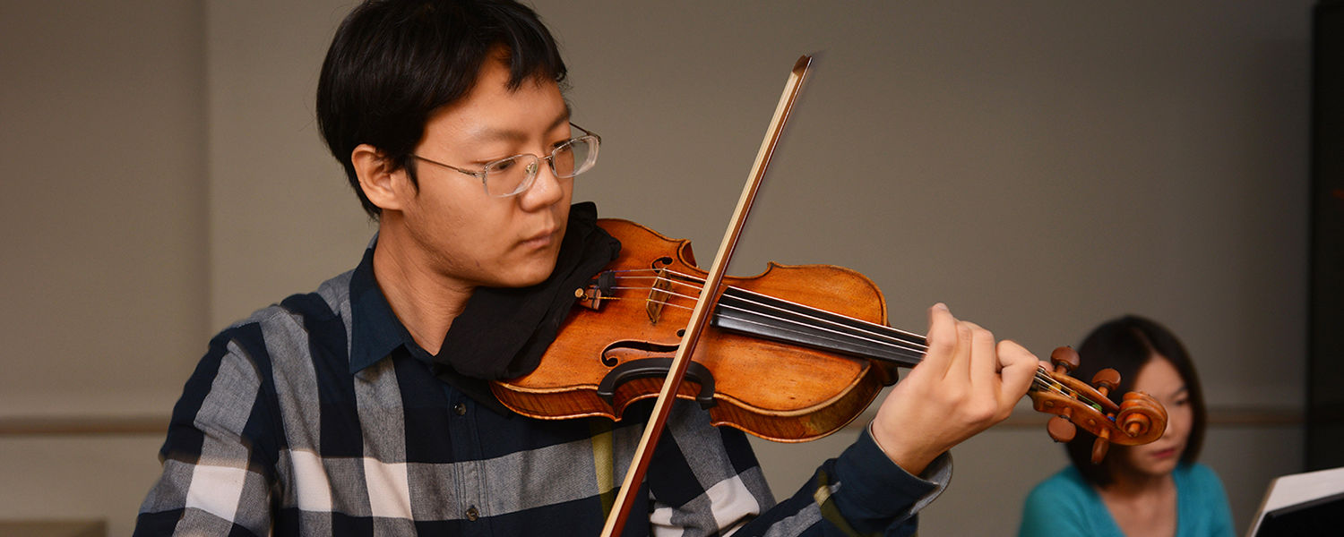Kent State University senior music performance major Yang Zeng plays the violin during a performance.  Zeng has been offered a contract to be part of the first violin section of the Akron Symphony.