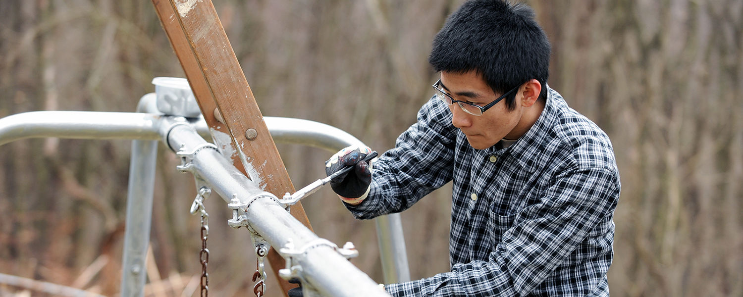 A Kent State student volunteer works on repairing playground equipment in East Liverpool during a Kent State alternative spring break trip.