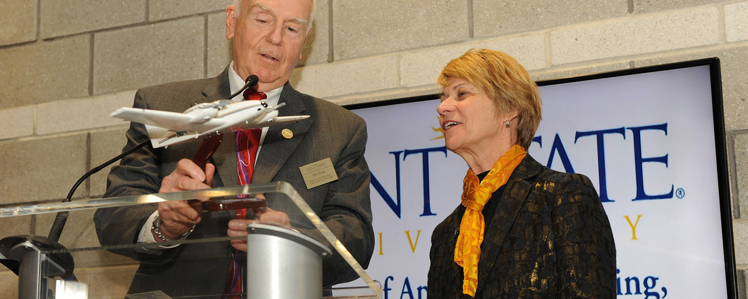 Bob Sines, interim dean of the College of Applied Engineering, Sustainability and Technology, gives a gift to Kent State President Beverly Warren during the grand opening of the college's new building.