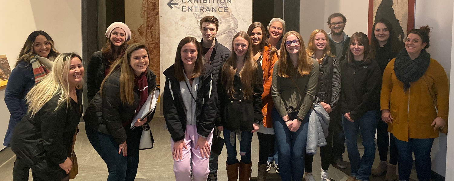 Students with professor at art exhibit