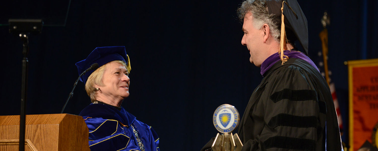 Kent State President Beverly Warren gives a gift of recognition to Kent State alumnus David Webster, who was the speaker at the morning Fall Commencement ceremony.