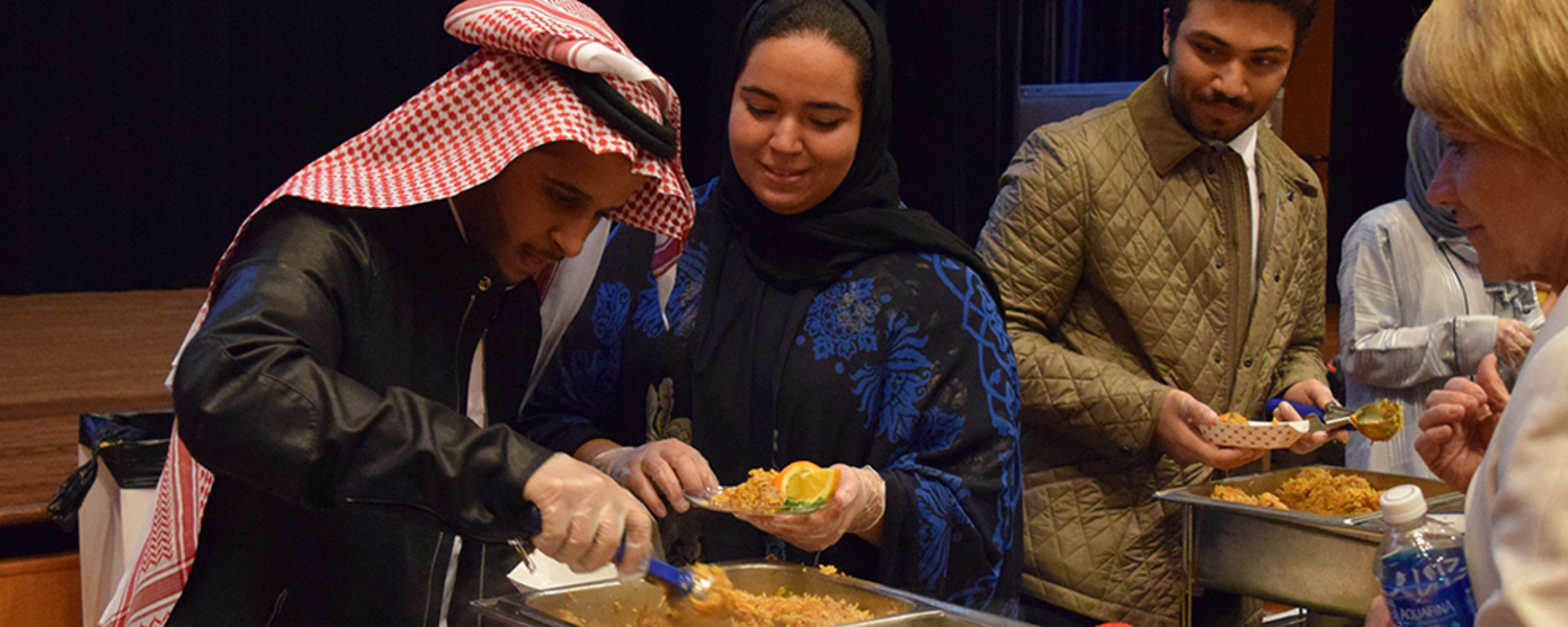President Warren samples a dish prepared by first place winner, Team Saudi Arabia