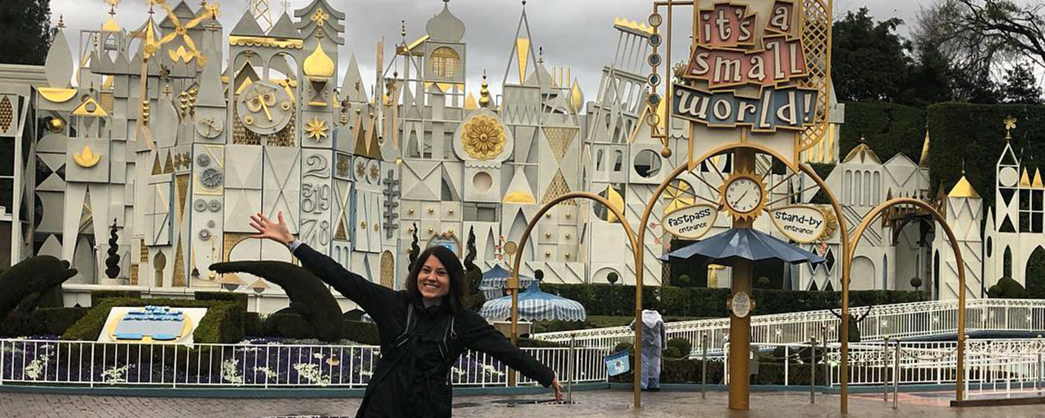 UXD Disney employee in front of its a small world ride.