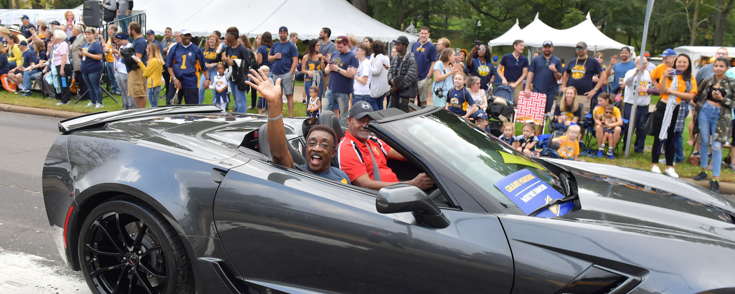 Homecoming Parade Grand Marshal Wayne Dawson, a Kent State alumnus and WJW Fox 8 anchor, waves to the crowd from the seat of a Corvette during the parade.