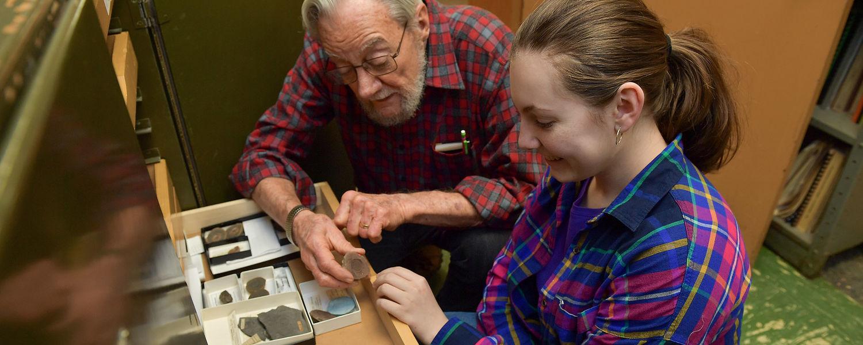 Professor Emeritus of Geology Rodney Feldmann, Ph.D., and Megan Schinker, a senior at Stow-Munroe Falls High School, examine a 300-million-year-old cyclid specimen in Dr. Feldmann's lab in McGilvrey Hall.