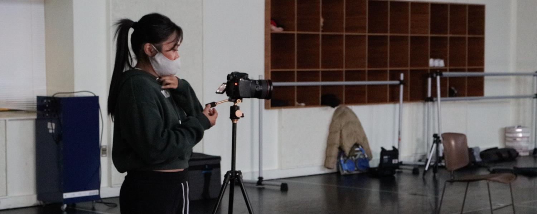 Student videographer in dance studio