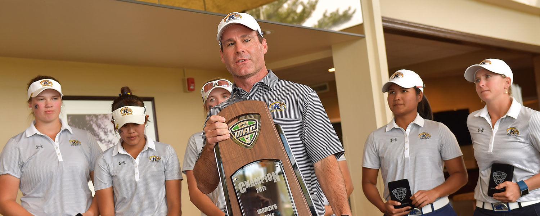 Greg Robertson, head coach of Kent State women's golf, holds the 2017 MAC Women's Golf Championship Trophy. Robertson was named MAC Coach of the Year.