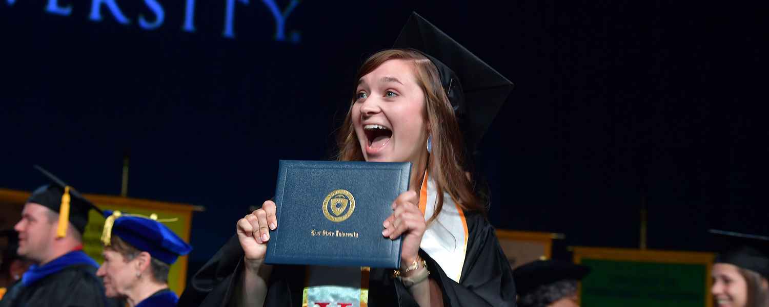 The gonfalon bearer from Kent State's College of Nursing crosses the stage and gives her family a smile during Summer 2018 Commencement.